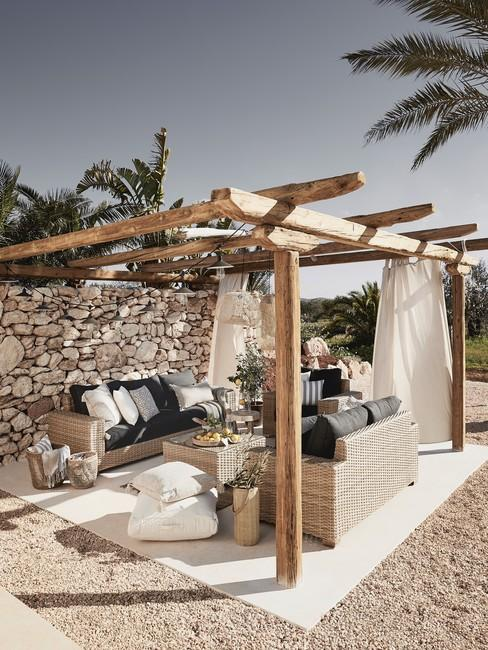 Houten pergola in ibiza stijl met zandkleur meubels tegen stenen muur