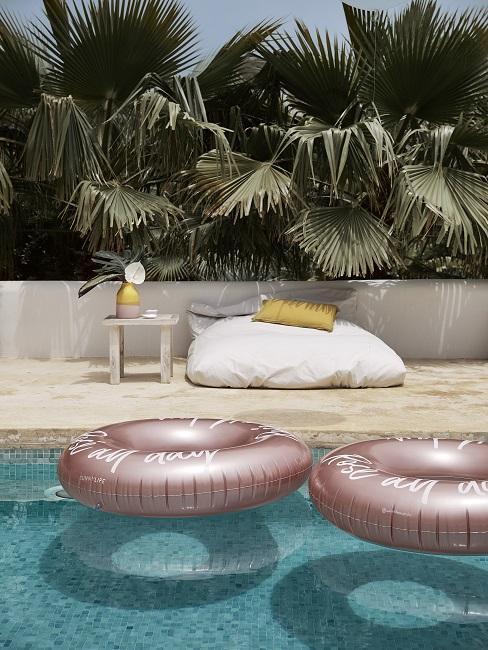 Zwembad met roze zwembanden met op de achtergrond tropische planten
