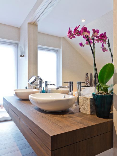 Łazienka w stylu japońskim. Umywaliki na drewnianej podstawie, obok storczyk