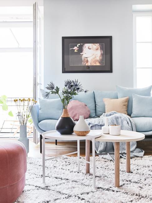 Fragment salonu w stylu skandynawskim z błękitną sofą, białym stolikiem kawowym, kolorowymi poduszkami oraz kwiatami