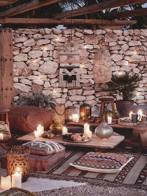 Taras w stylu boho z kamienną ścianką działową, poduszkami oraz latarenkami