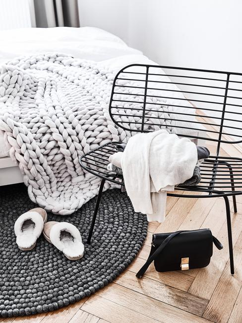 Fragment sypialnia z łóżkiem, czarnym, okrągłym dywanikiem oraz czarnym, metalowym krzesłem
