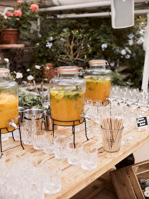 Zastawiony, drewniany stół z trzema słojami mrożonej herbaty oraz szklankami i innymi akcesoriami
