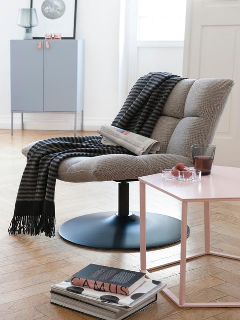 Minimalistyczny, szary fotel, na którym leży książka