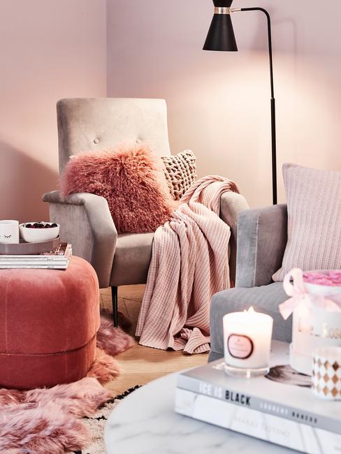 Kącik do czytania z elementami pudrowego różu oraz brzoskwini. Fotel z miękką poduszką i kocem.