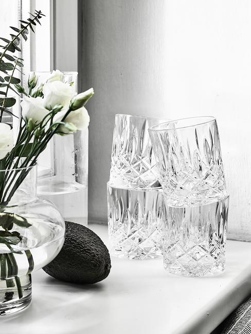 Parapet udekorowany kwiatami w wazonie, czterema kryształowymi szklankami oraz awokado