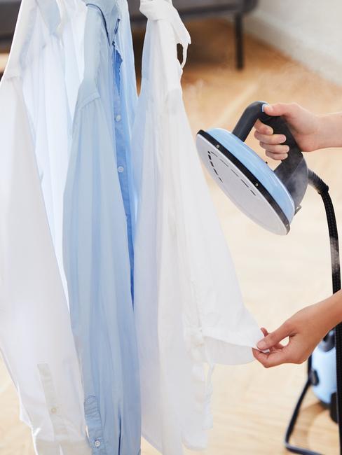Koszule wiszące na wieszaku i żelazko parowe