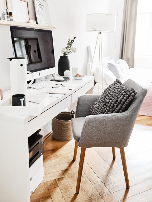 Białe biurko z komputerem oraz szarym krzesłem