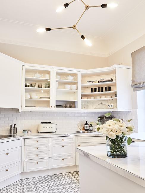 Biała kuchnia z wiszącymi szafkami, wyspą kuchenną oraz sprzętem AGD