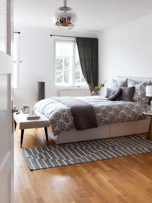 Biała sypialnia z szarymi dodatkami w postaci poduszek, narzuty oraz zasłon