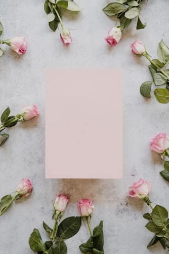 Różowa kartka leżąca na marmurowym stole wokół róż