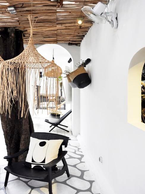 Czarne krzesło z poduszką, wiszącymi dekoracjami na zewnątrz domu