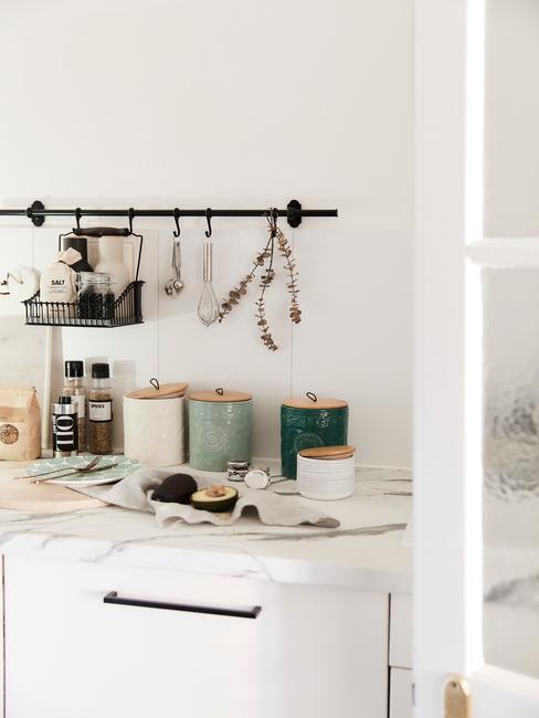 Fragment białej kuchni z blatem, na którym leżą akcesoria kuchenne