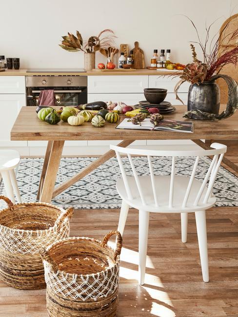 Kuchnia w stylu skandynawskim z drewnianym stołem, białym krzesłem oraz koszami z rattanu