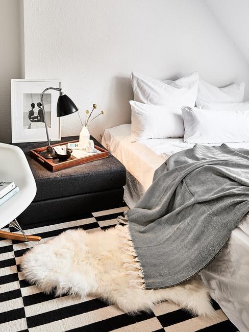 Fragment białego łóżka z szarą narzutą, czarnym pufem oraz lampką nocną