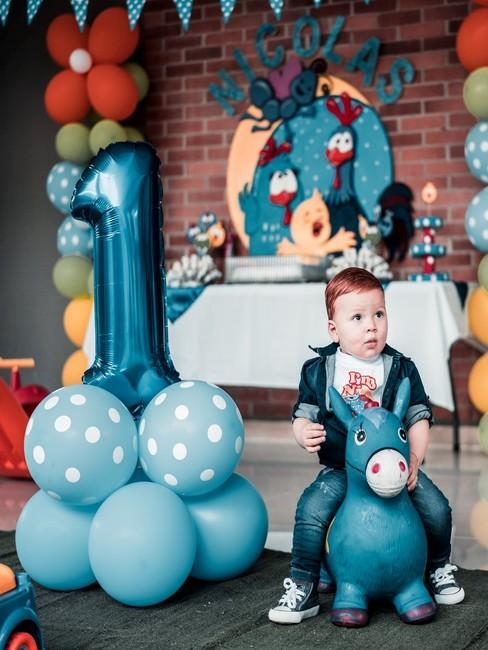 Chłopczyk siedzący na zabawkowym koniu obok niebieskiej dekoracji z balonów