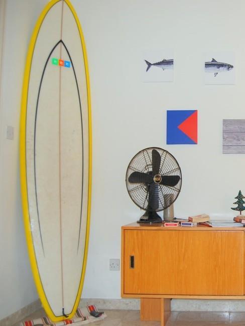 Pomieszczenie z deską surfingową, komodą oraz wiatrakiem