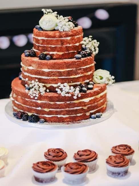 Minimalistyczny, trzywarstwowy tort udekorowany kwiatami ułożony na białej paterze