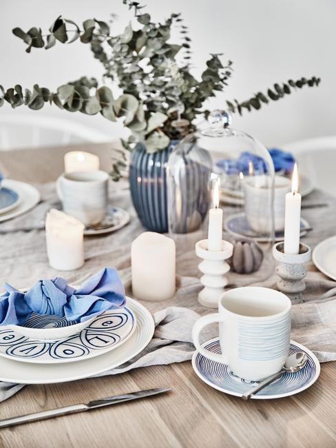 Zastawiony drewniany stół niebiesko-białą zastawą oraz wazonem z eukaliptusem