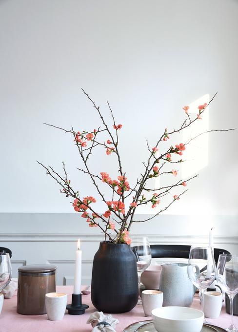 Stoł nakryty pudrowo-różowym obrusem, wazon zkwitnącymi gałązkami