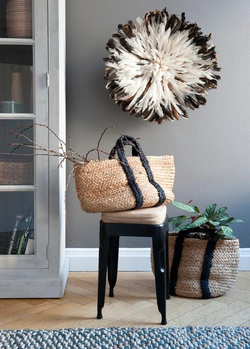 Krzesło z plecionym koszem, w tle ściana z dekoracyjną rzeźbą przestrzenną