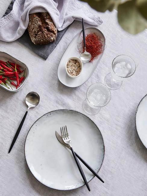Zastawa kuchenna w stylu skandynawskim położona na białym obrusie obok półmiska z jedzeniem