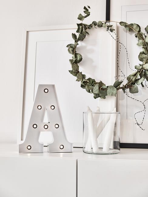 Zbliżenie na biała ozdobną literę, świecznik, ramkę na zdjęcia oraz wianek z eukaliptusa