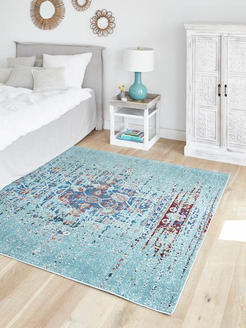 Biała sypialnia z łóżkiem o szarym zagłówku, stolikiem nocnym oraz niebieskim dywanem