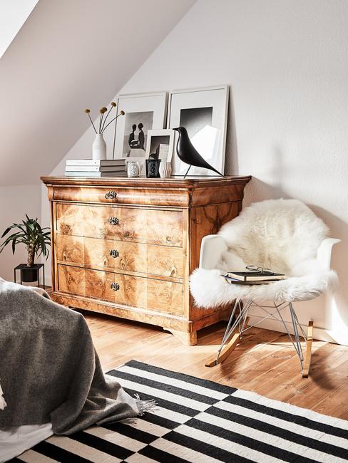 Sypialnia na poddaszu z łożkiem, dywanem z czarno-białe pasy oraz drewnianą komodą