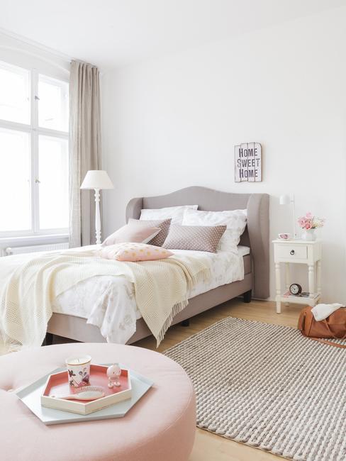 Biała sypialnia z łóżkiem z szarym zagłówkiem. Obok jasny dywan