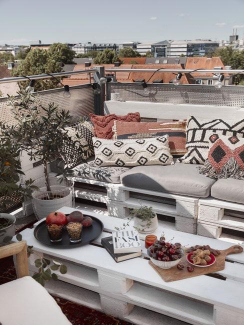 Balkon w bloku z meblami z palet i wzorzystymi poduszkami