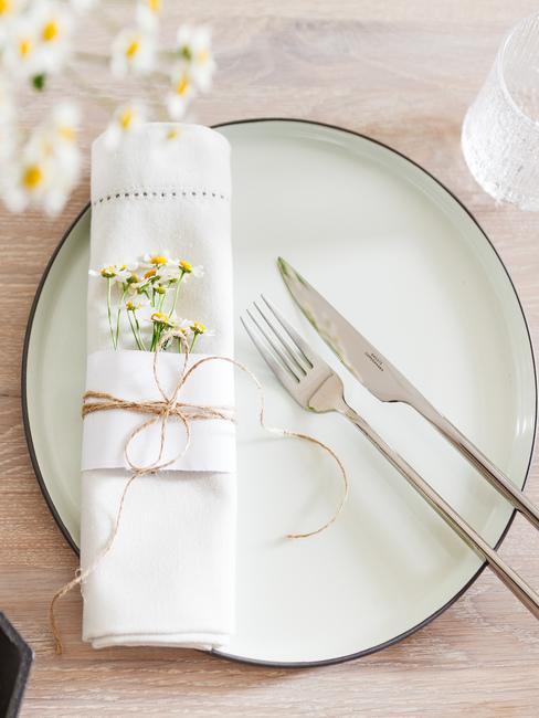 Talerz z lnianą serwetką przewiazaną sznureczkiem, ozdobioną kwiatami