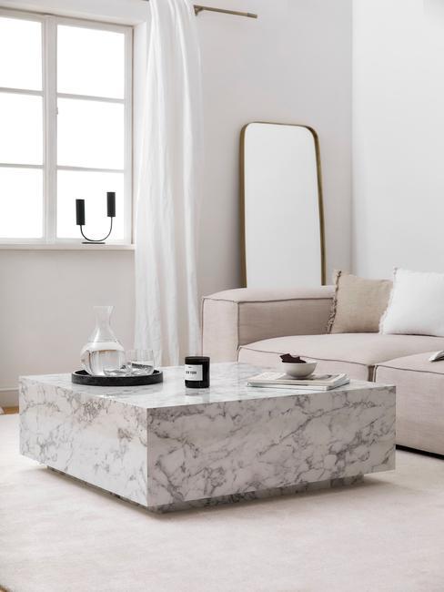 Biały salon z marmurowym stolikiem kawowym, beżową kanapą oraz dekoracjami