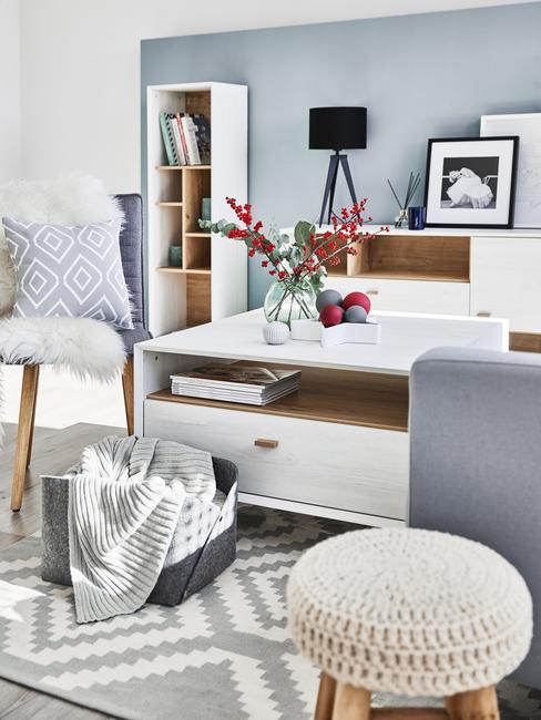 Błękitny salon w stylu skandynawskim z białymi meblami, szarymi dodatkami oraz kontrastującą, czarną lampą