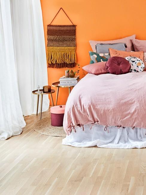 Sypialnia w stylu boho z pomarańczową ścianą oraz pościelom w kolorze różu