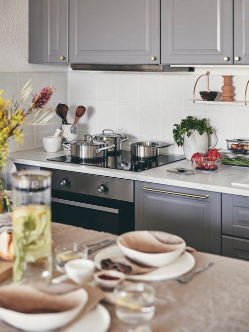 biała kuchnia z szarymi meblami kuchennymi i kolorowymi akcesoriami
