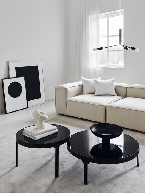 Designerski salon w czarno-białych barwach z grafikami opartymi o ścianę