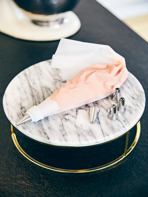 Rękaw cukierniczy wypełniony kremem na podstawce do tortu