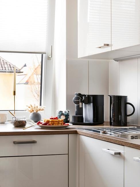 Biała kuchnia z drewnianym blatem oraz czarnym sprzętem kuchennym