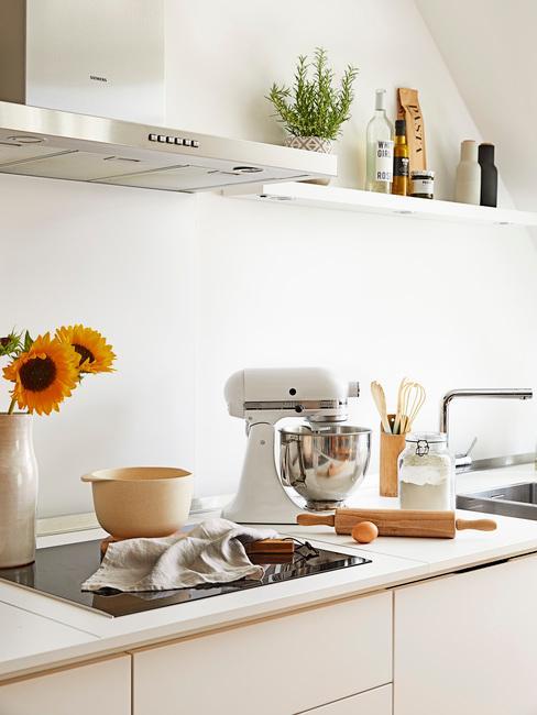 Biała kuchnia z białym blatem, na której znajduje się robot kuchenny, wazon z kwiatami a nad nim półka z rozmarynem
