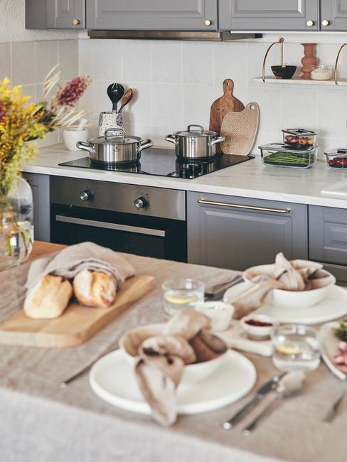 Biała kuchnia z szarymi meblami, wyspą kuchenną oraz akcesoriami