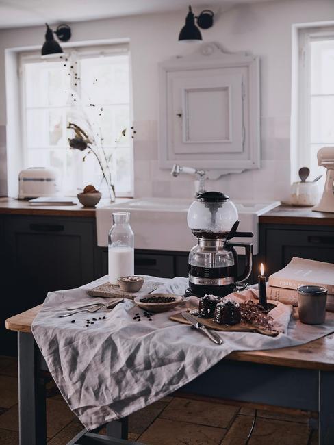 Biała kuchnia z czarnymi meblami, drewnianym dlatem oraz wyspą kuchenną, na której znajduje się ekspres do kawy