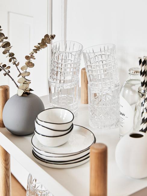 Biały wózek barowy, na którym znajduje się zastana kuchenna, szklanki do wody oraz mały wazon z eukaliptusem
