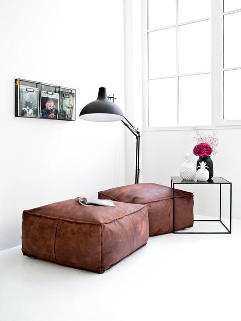 Minimalistyczne wnętrze z dwoma, skórzanymi pufami oraz stolikiem kawowym