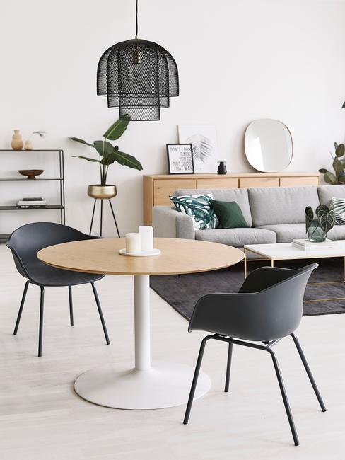 Jasny salon połączony z jadalną z drewnianym, okrągłym stołem, czarnymi krzesłami, szarą sofą i roslinami