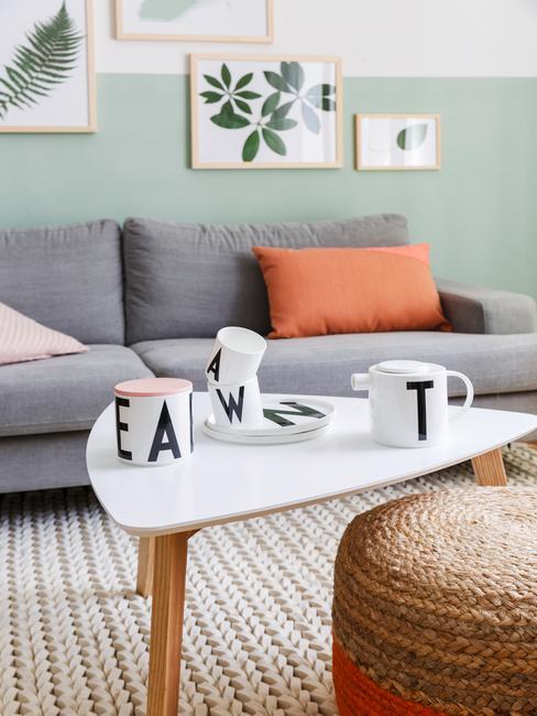 Salon z zieloną ścianą, szarą sofą oraz białym stolikiem kawowym