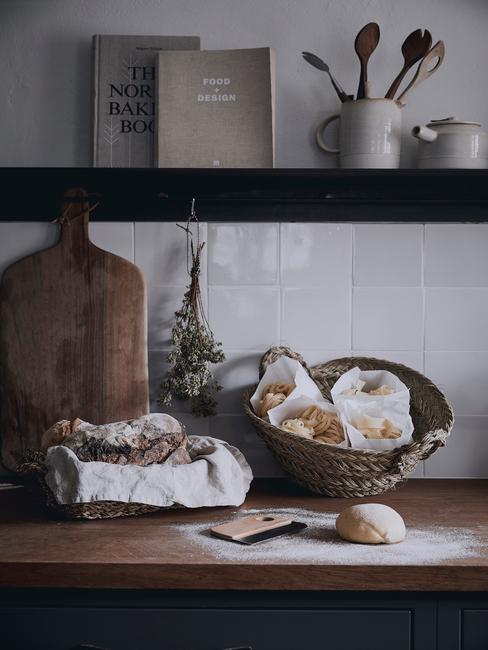 Biała kuchnia wyłożona kafelkami z czarną półką z książkami kucharskimi