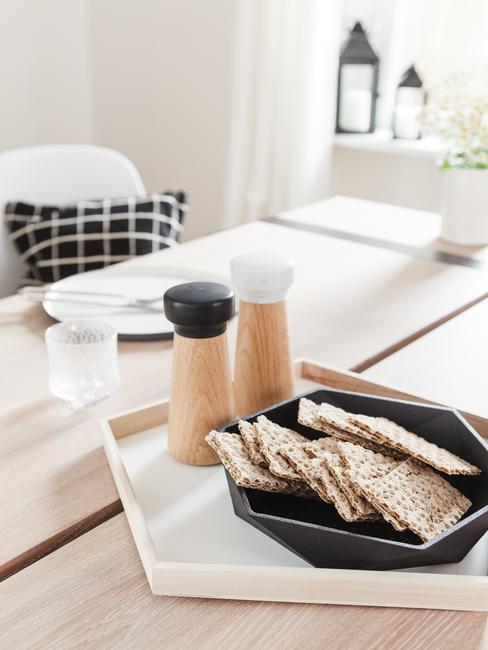 Zbliżenie na drewniany stoł na którym jest prosta, zastawa kuchenna