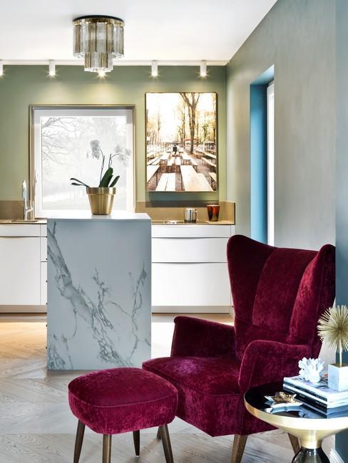 Kuchnia w stylu glamour z marmurową wyspą kuchenną oraz karmazynowym krzesłem wypoczynkowym