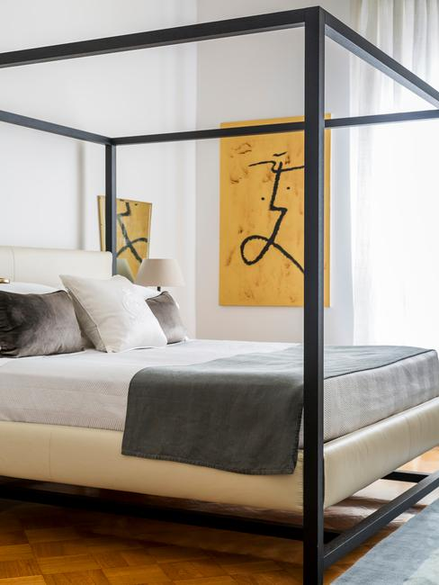 Biała sypialnia z nowoczesnymi grafikami na ścianie i łóżkiem w stylu industrialnym
